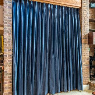 デンバーの大きいトラディショナルスタイルのおしゃれな独立型ダイニング (茶色い壁、無垢フローリング、両方向型暖炉、レンガの暖炉まわり、赤い床) の写真