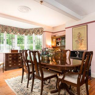 Esempio di una sala da pranzo chic chiusa e di medie dimensioni con pareti rosa, pavimento in legno massello medio, stufa a legna e pavimento marrone