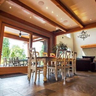 Ejemplo de comedor de cocina retro, grande, con paredes blancas, suelo de madera clara, chimenea tradicional, marco de chimenea de hormigón y suelo multicolor