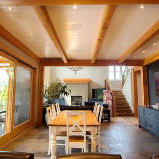 Imagen de comedor de cocina vintage, grande, con paredes blancas, suelo de madera clara, chimenea tradicional, marco de chimenea de hormigón y suelo multicolor