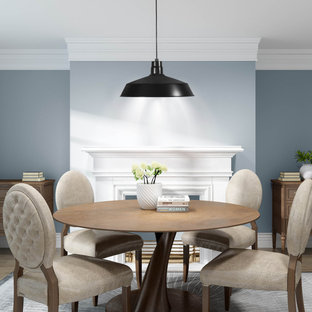 Immagine di una piccola sala da pranzo aperta verso la cucina classica con pareti blu, parquet chiaro, camino classico, cornice del camino in legno e pavimento grigio