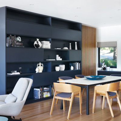 Example of a large trendy medium tone wood floor and brown floor great room design in Sydney with white walls and no fireplace
