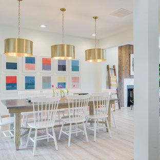 Immagine di una grande sala da pranzo aperta verso il soggiorno country con pareti bianche, pavimento in laminato, camino classico, cornice del camino in pietra e pavimento marrone