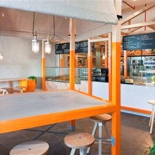 Ispirazione per una grande sala da pranzo aperta verso la cucina nordica con pareti arancioni e pavimento in ardesia