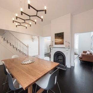 メルボルンの中くらいのトラディショナルスタイルのおしゃれな独立型ダイニング (白い壁、濃色無垢フローリング、標準型暖炉、木材の暖炉まわり、黒い床) の写真