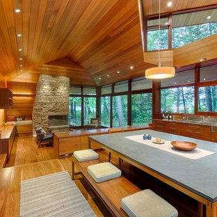 Mittelgroße Moderne Wohnküche mit braunem Holzboden, Tunnelkamin und Kaminumrandung aus Stein in Boston