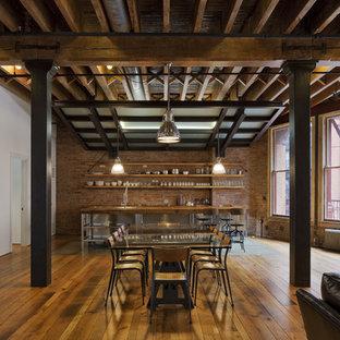 Foto di una sala da pranzo aperta verso il soggiorno industriale di medie dimensioni con pavimento in legno massello medio e pareti multicolore
