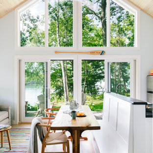 This is an example of a small country open plan dining room in Portland Maine with blue walls, light hardwood flooring, no fireplace and brown floors.