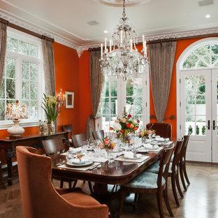 Idee per una sala da pranzo tradizionale chiusa con pareti arancioni e pavimento in legno massello medio
