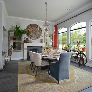 This is an example of a large eclectic kitchen/dining room in Houston with grey walls, dark hardwood flooring, a standard fireplace, a stone fireplace surround and grey floors.