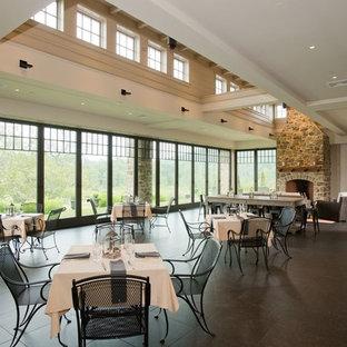 Ispirazione per un'ampia sala da pranzo aperta verso il soggiorno con pareti bianche, pavimento in gres porcellanato, camino classico, cornice del camino in pietra e pavimento nero