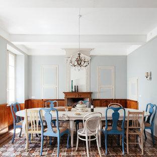 Foto di una grande sala da pranzo mediterranea chiusa con pareti grigie, camino classico e cornice del camino in legno