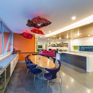 Cette image montre une grande salle à manger ouverte sur la cuisine minimaliste avec un mur orange, béton au sol et un sol gris.