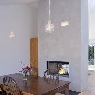 Новый формат декора квартиры: столовая в стиле современная классика с серыми стенами, светлым паркетным полом и двусторонним камином