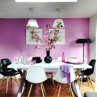 Réalisation d'une salle à manger design avec un mur rose et un sol en bois brun.
