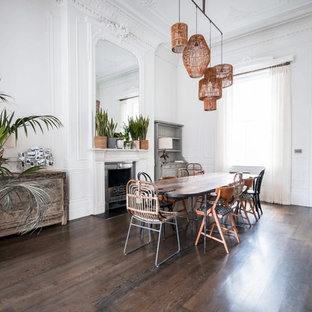 Large eclectic enclosed dining room in London with white walls, a standard fireplace, a plastered fireplace surround, dark hardwood flooring and brown floors.