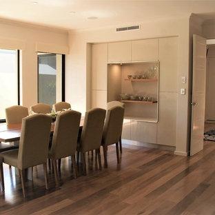 Aménagement d'une grand salle à manger ouverte sur le salon moderne avec un mur blanc, un sol en bois clair et un sol jaune.