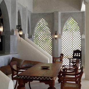 他の地域の広いトロピカルスタイルのおしゃれなLDK (グレーの壁、コンクリートの床、白い床) の写真