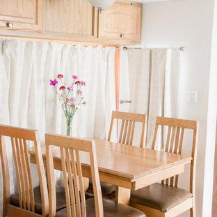 Immagine di una piccola sala da pranzo aperta verso il soggiorno bohémian con pareti arancioni
