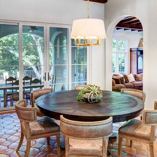 Aménagement d'une salle à manger ouverte sur la cuisine méditerranéenne de taille moyenne avec un mur blanc et un sol en carreau de terre cuite.