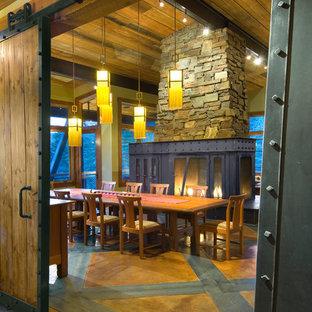 Ispirazione per una grande sala da pranzo rustica chiusa con pareti beige, pavimento in cemento, stufa a legna, pavimento multicolore e cornice del camino in metallo