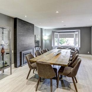Foto di un'ampia sala da pranzo aperta verso la cucina minimal con pareti grigie, pavimento in gres porcellanato, camino classico, cornice del camino piastrellata e pavimento grigio