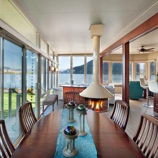 Immagine di una sala da pranzo aperta verso il soggiorno chic con pareti beige, camino sospeso, cornice del camino in metallo e pavimento grigio
