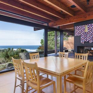 Réalisation d'une grand salle à manger ouverte sur le salon asiatique avec une cheminée double-face, un manteau de cheminée en béton, un sol en bambou et un sol beige.