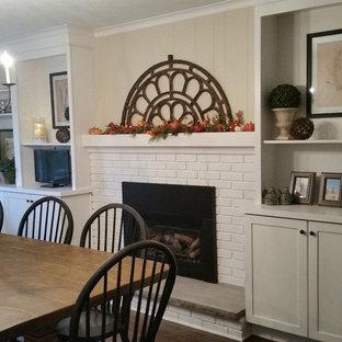 Cette image montre une salle à manger rustique de taille moyenne et fermée avec un mur beige, une cheminée standard, un manteau de cheminée en brique, un sol marron et un sol en vinyl.