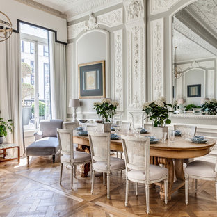 Traditional dining room in London with grey walls and medium hardwood floors.