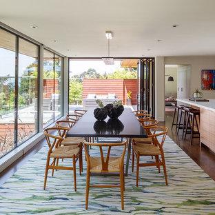 Cette photo montre une grand salle à manger ouverte sur la cuisine rétro avec un mur blanc, un sol en bois brun et un sol turquoise.