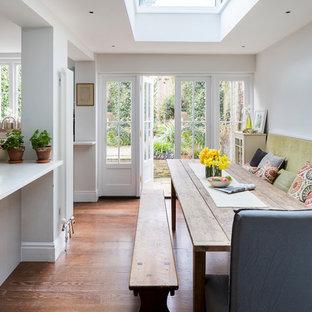 Пример оригинального дизайна: кухня-столовая в классическом стиле с белыми стенами, паркетным полом среднего тона и коричневым полом