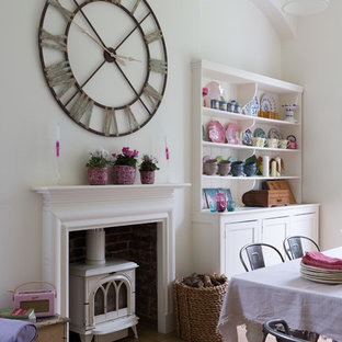 Example of a cottage chic dining room design in London with white walls and a wood stove