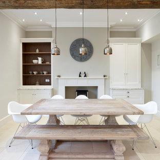 Foto di una sala da pranzo aperta verso la cucina classica di medie dimensioni con pareti beige, pavimento con piastrelle in ceramica, camino classico e cornice del camino in intonaco