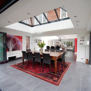 Inspiration pour une grand salle à manger ouverte sur la cuisine design avec un mur blanc et un sol en ardoise.