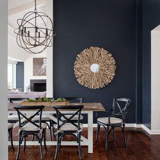 Idées déco pour une grand salle à manger ouverte sur la cuisine bord de mer avec un sol en bois foncé et un mur bleu.