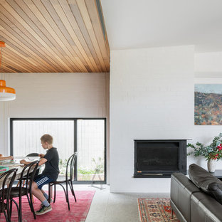 Ispirazione per una sala da pranzo aperta verso il soggiorno design di medie dimensioni con pareti bianche, pavimento in cemento, stufa a legna, cornice del camino in mattoni e pavimento grigio