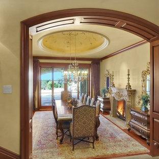 На фото: огромная отдельная столовая в классическом стиле с бежевыми стенами, паркетным полом среднего тона, стандартным камином, фасадом камина из бетона и коричневым полом с