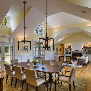 Idee per una sala da pranzo aperta verso il soggiorno classica con pareti gialle e pavimento in legno massello medio