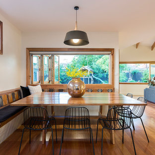 Inspiration for a large midcentury open plan dining in Melbourne with white walls, medium hardwood floors and brown floor.