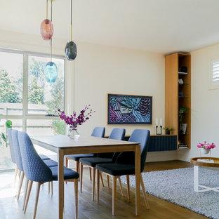 Contemporary open plan dining in Melbourne with beige walls, medium hardwood floors and brown floor.