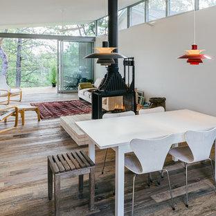 Esempio di una sala da pranzo aperta verso il soggiorno contemporanea con pareti bianche, pavimento in legno massello medio e stufa a legna