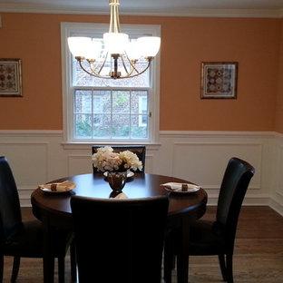 Foto di una piccola sala da pranzo tradizionale chiusa con pareti arancioni, pavimento in legno massello medio e nessun camino