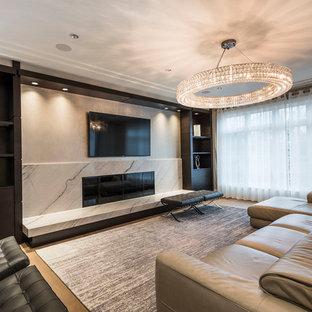 Immagine di una grande sala da pranzo aperta verso il soggiorno design con pareti beige, parquet chiaro, camino lineare Ribbon, cornice del camino in pietra e pavimento beige