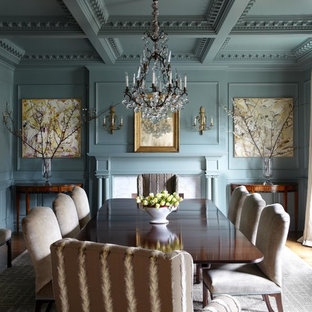 Ispirazione per una sala da pranzo chic chiusa e di medie dimensioni con pareti blu, pavimento in legno massello medio e camino classico