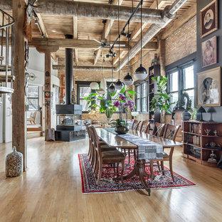 Ejemplo de comedor industrial, de tamaño medio, abierto, con paredes multicolor, suelo de madera en tonos medios, suelo marrón y estufa de leña