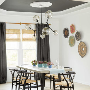 Example of an eclectic light wood floor and beige floor enclosed dining room design in Nashville with white walls