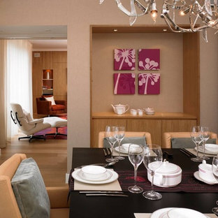 Contemporary dining room in London with beige walls and medium hardwood flooring.