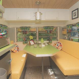 Esempio di una piccola sala da pranzo aperta verso la cucina bohémian con pareti grigie, pavimento in vinile e pavimento grigio