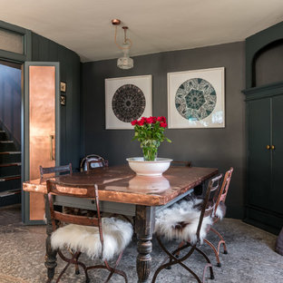 Dining room - mid-sized industrial gray floor dining room idea in Other with black walls